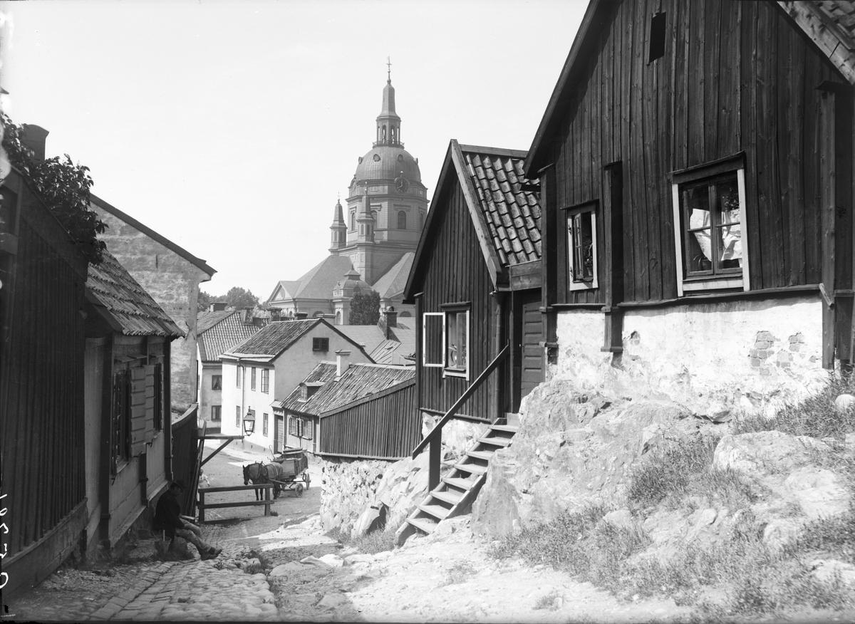Parti av Södermalm i Stockholm. Trähus vid Sandbacksgatan, dåvarande Stigbergsgatans västra del. I bakgrunden syns Katarina kyrka.