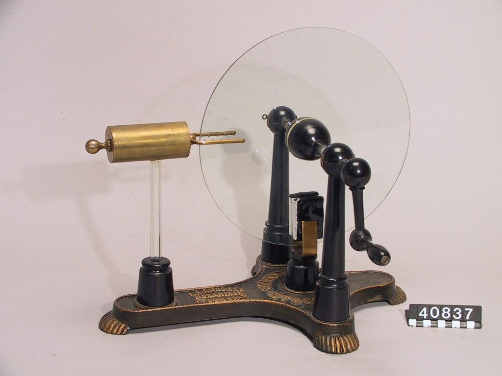 """Friktionselektricitetsmaskin. Foten märkt: """"F.F. Lundell, Mekaniker, Stockholm"""" och """"Svanström & Co, Stockholm""""."""