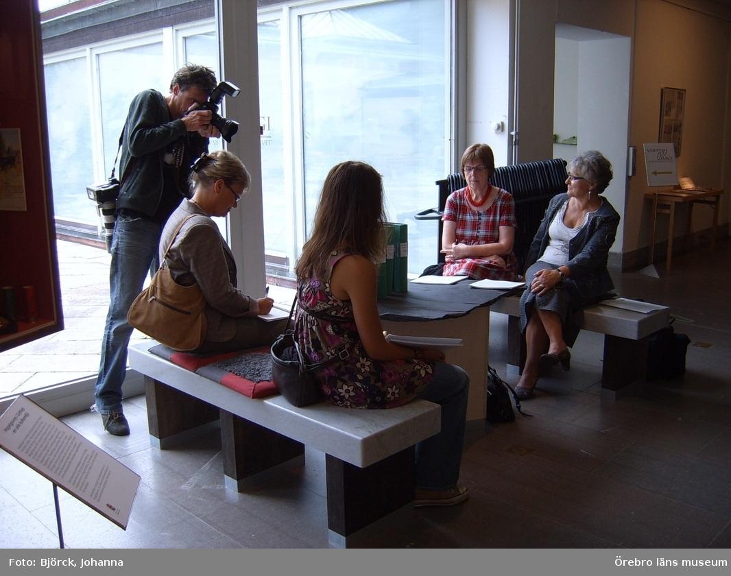 """Bilder tagna i samband med pressinformation om dokumentationsprojektet """"Brevet till framtiden"""". Se Dnr: 2004.910.194 för vidare upplysningar om projektet.Vid fönstret fotograf Per Knutsson, Nerikes Allehanda.Sittande till höger med ryggen mot kameran (bredvid fotografen) Inger Nordahl samt bredvid henne skrivaren nr. 77: Johanna Alkärr.Sittande vända mot kameran vid fönstret skrivare nr. 54: Carine Matsubara. Bredvid henne Irena Westberg som medverkat i projektet i en intervju utförd 2005.09.26.Plats: Nyhetsrummet, Örebro läns museum, den 23 augusti 2007."""