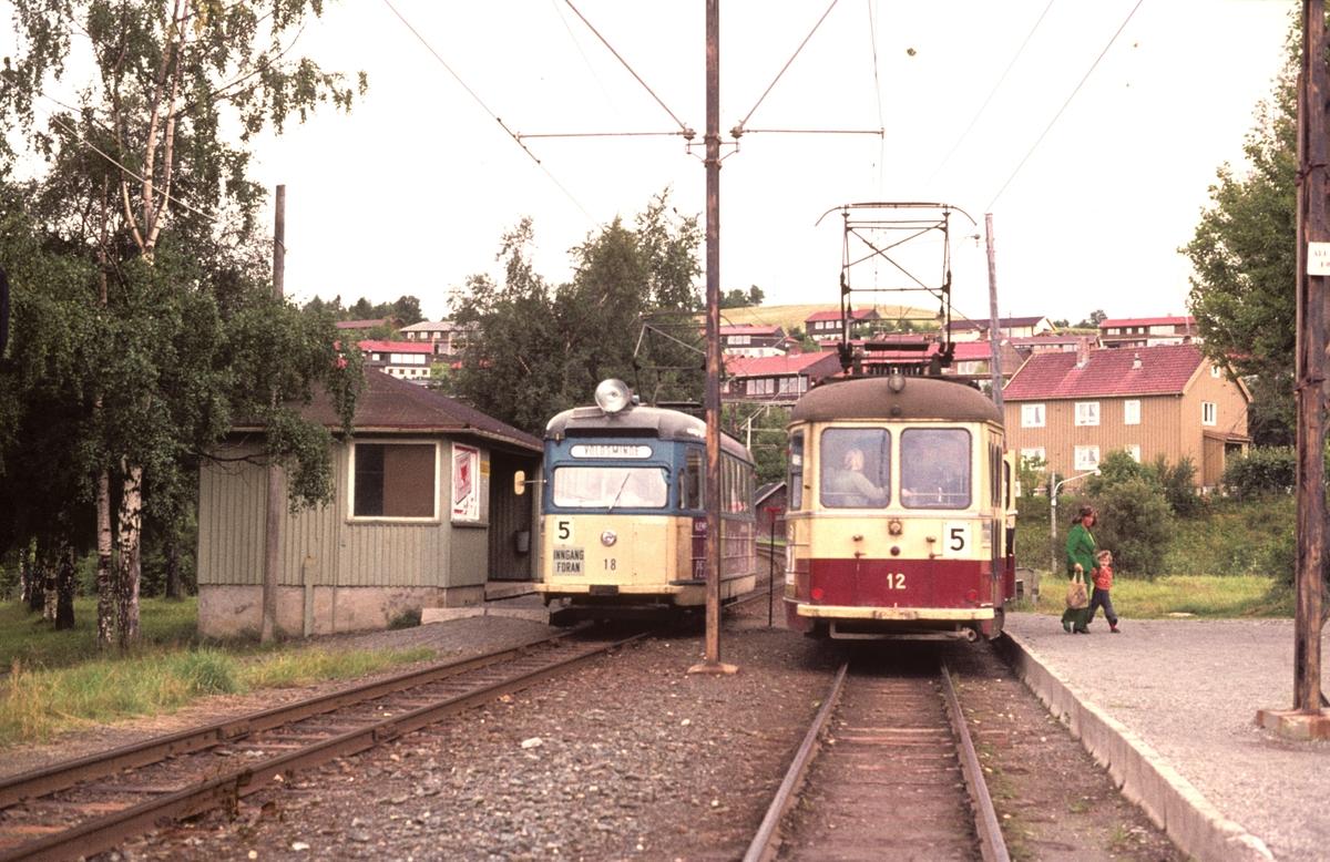 To trikker møtes på Breidablikk på Gråkallbanen. Strømmenvogn 12 i nye farger og 18 i de gamle.
