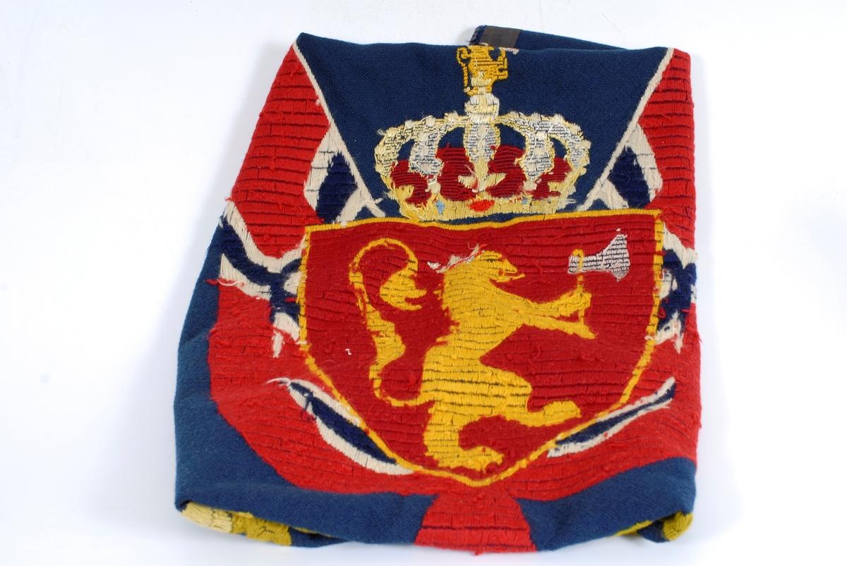 det kongelig norske riksvåpen med et flagg på hver side og eikeblader