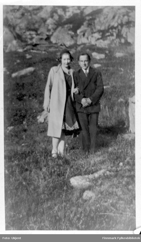 Dette bildet er av Vilmar Dahl og en ukjent kvinne. Vilmar muligens fra Øksfjord, Loppa kommune. Kvinnen er kledd i en lang frakk, et hodeplagg, kjole og har på seg et smykke. Vilmar er kledd i jakke, bukse og slips. I bakgrunnen kan man se stein.