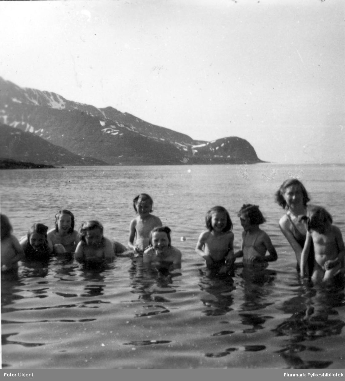 Barn bader i sjøen. Bildet er muligens tatt på badestranda i Nuvsvåg. Jenta i badedrakt som er nummer to fra høyre er muligens Irene Martinsen. Man kan se fjell i bakgrunnen.