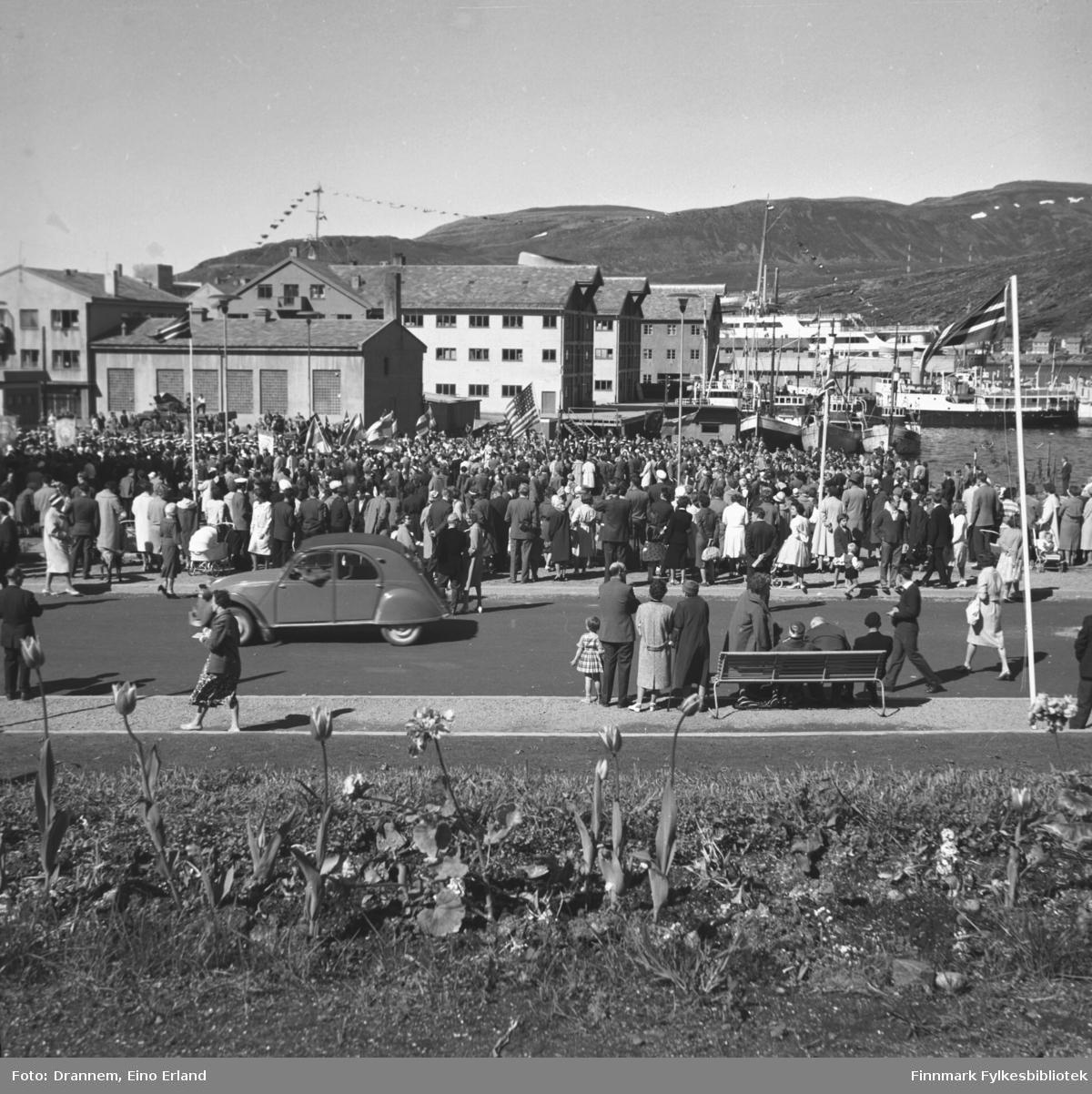 """En stor folkemengde på rådhusplassen i Hammerfest i regi av norsk-finsk forening. Noen bærer finske og amerikansk flagg og 6th Army Corps ses til venstre blant folkemengden. Det store skipet som ligger ved Dampskipskaia kan være Den Norske Amerikalinjens båt """"Oslofjord"""""""