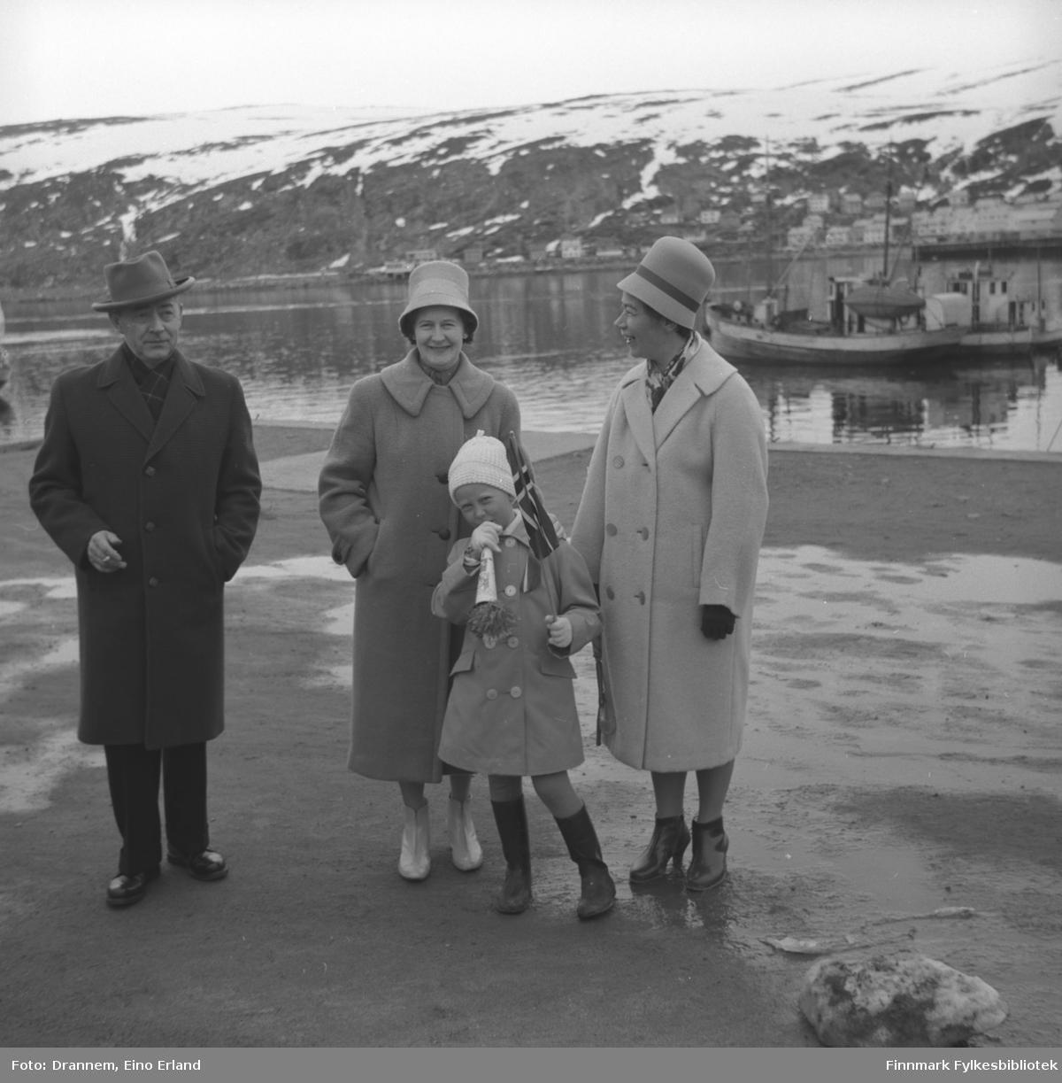 Fire personer på Dampskipskaia i Hammerfest, sannsynligvis 17. mai siden jenta har flgg og fløyte i hendene. Jenny Drannem står helt til høyre på bildet, de tre andre er familien Sørensen.