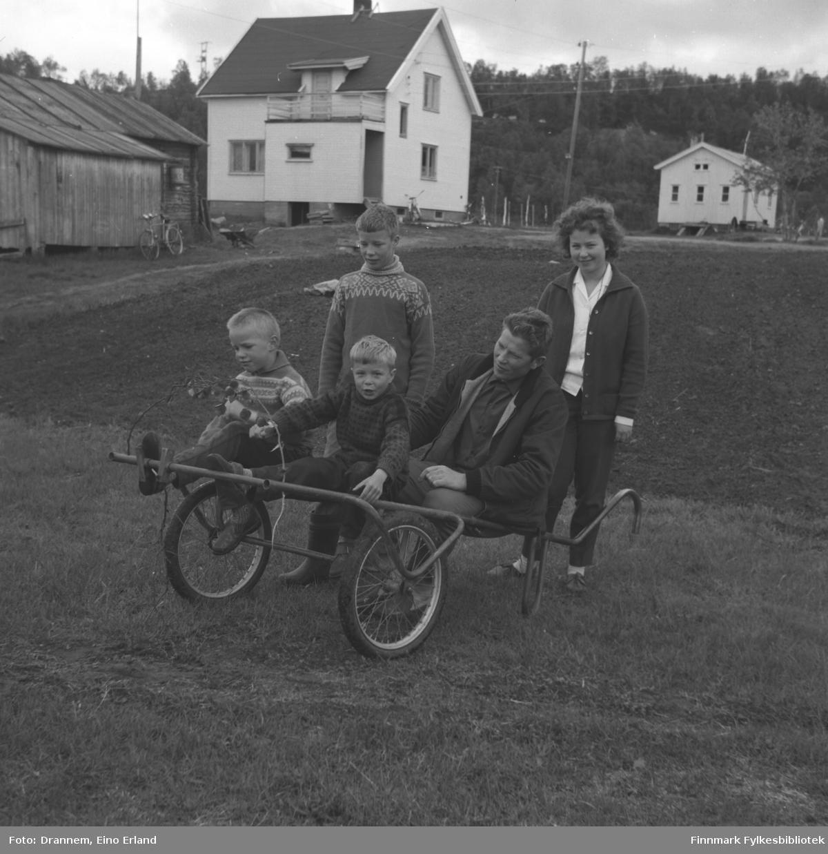 Tre gutter, i tillegg til Oskar Karikoski og Turid Karikoski, på og rundt en vogn.