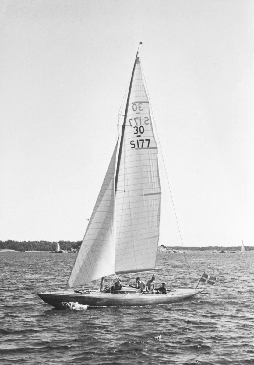 Fartyg: KORYBANT                       Bredd över allt 2,18 meter Längd över allt 13,26 meter  Rederi: Hedborg, Ingeborg Byggår: 1939 Varv: Kungsörs Båtvarv (Oscar Schelin) Konstruktör: Reimers, Knud H. Övrigt: Denna bild illustrerar i KSSS årsbok 1944 att 30-S177 KORYBANT året innan erövrade The Marblehead Trophy; om bilden är tagen i samband med dessa seglingar eller vid annat tillfälle är dock ovisst. Det kan noteras att det före kriget byggdes två Reimers-ritade SK30:or som båda fick segelnummer 30-S177; den första var ROULETTE VII (b. 1938 på Motala Båtvarv), som såldes utomlands; den andra var KORYBANT. Dess förste ägare var Erik Lundberg, men vid tiden för seglingarna om The Marblehead Trophy  i juli 1943 ägdes båten av Ingeborg Hedlund (rorsman under seglingarna var dock Oscar Plym). Efter kriget såldes KORYBANT till England. Fotografiet återgivet som försättsplansch i KSSS årsbok 1944.