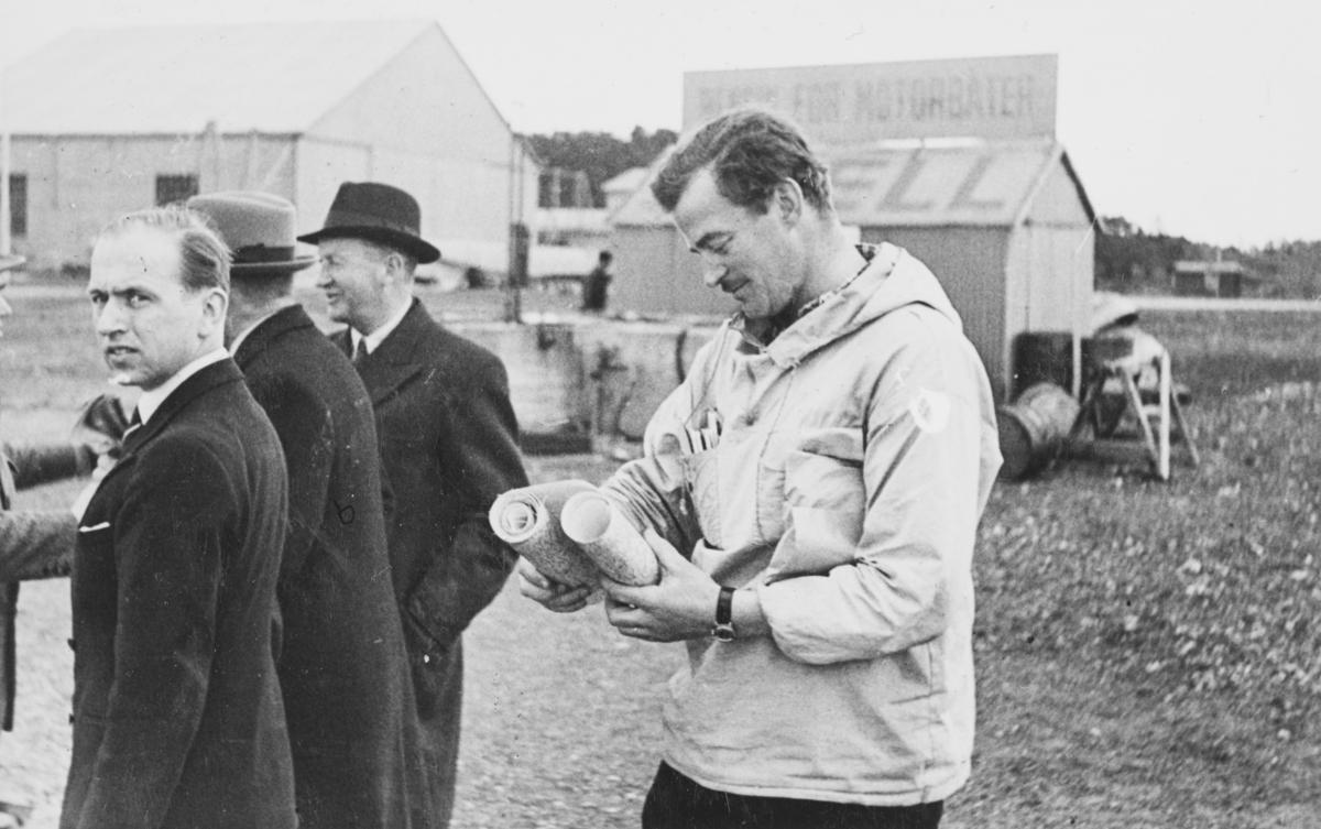 Flyveren Hans Grøn Lund t.h. studerer ruten for ambulanseflyet til Nord-Norge. Ellef Ringnes med hatt-