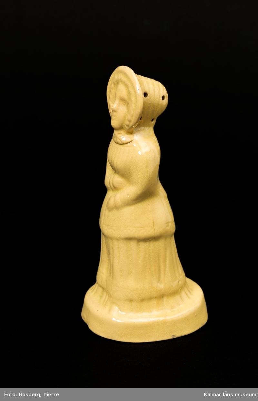 KLM 9319 Strödosa, peppardosa av lergods, gul skärv, glaserad. Benämnd fajans. I form av en kvinna i dräkt från 1840-50-tal. I hatten ett flertal hål för funktion som ströare. Runt hål i botten för påfyllning.