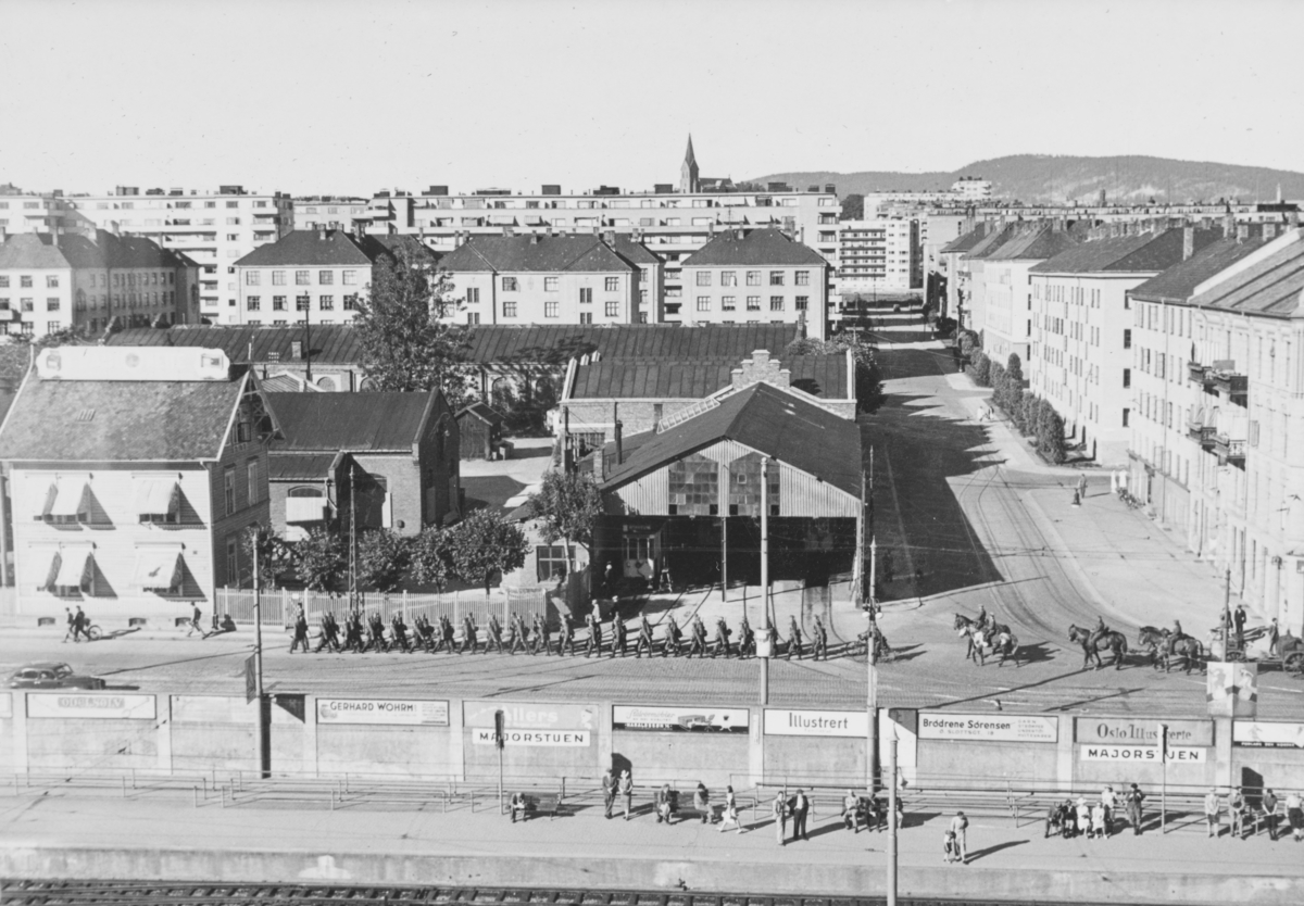 Majorstuen stasjon på Holmenkolbanen. I bakgrunnen tyske tropper, på vei oppover Slemdalsveien. Midt på bildet den gamle trikkestallen.