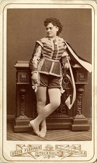 """Rollporträtt (helfigur) av operasångerskan Carolina Östberg i mansdräkt med cape.Carolina Östberg -  1853-1929, var en svensk operasångerska.Hon var dotter till en fältskär och visade tidigt musikalisk begåvning, som hon utvecklade på Dramatens elevskola 1869-1873. Hon var elev till Signe Hebbe. Hon visade sin talang som konsertsångare innan hon debuterade på Stora Teatern 1873 tillsammans med Louise Pyk med varsin roll i samma pjäs. De gjorde båda succé; Östbergs röst ansågs som en frisk klar och ren timbre, en svag men ren sopran med bra koloraturisk träning, och hon hälsades med jubel av publiken i mansrollen Carlo Broschi i """"Hälften var"""" 1874, varefter hon fick fast anställning; rollen som Carlo Broschi förblev hennes mest populära, och fram till hennes kontrakt utgick 1877 gjorde hon en rad stora roller och utvecklades mer för varje gång.Då kontraktet gick ut 1877 tänkte hon resa till Ryssland, men äktenskapet med grosshandlaren Horwitz 1878 fick henne att avsluta sin yrkesverksamhet, som det troddes för alltid. Hennes avgång ansågs vara en stor förlust; på kort tid hade hon blivit landets kanske mest populära operasångare.Då Carolina Östberg-Horwitz oväntat annonserades som gästskådespelare i titelrollen """"Boccaccio"""" på Nya Teatern 1879 drog förställningen fulla hus, och hon hälsades med så stor entusiasm att """"jublet aldrig ville ta slut""""; hon gjorde en stormande succé, kallades hjältinna och visade talang både i lättsamma operetter och mer allvarlig opera, och pressen uppmanade Operan att anställa henne. Hon turnerade i Köpenhamn 1880 och Tyskland 1882-1883 , Norge 1885 och tillhörde Nya Teatern fram till 1886. Hon använde sitt ursprungliga efternamn kallade sig själv fru Östeberg.År 1886 anställdes Östberg igen på Operan, vilket sågs som en triumf för publiken; """"publiken hade fått sin vilja fram"""" mot Operan, efter att i flera år krävt att hon skulle anställas där. Hon stannade sedan där, förutom en turné in USA 1892-94. Hon jämfördes med Louise Michaëli. Hon """