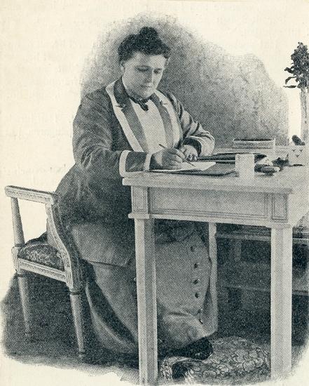Hon bär klänning. På bordet står en vas med blommor.