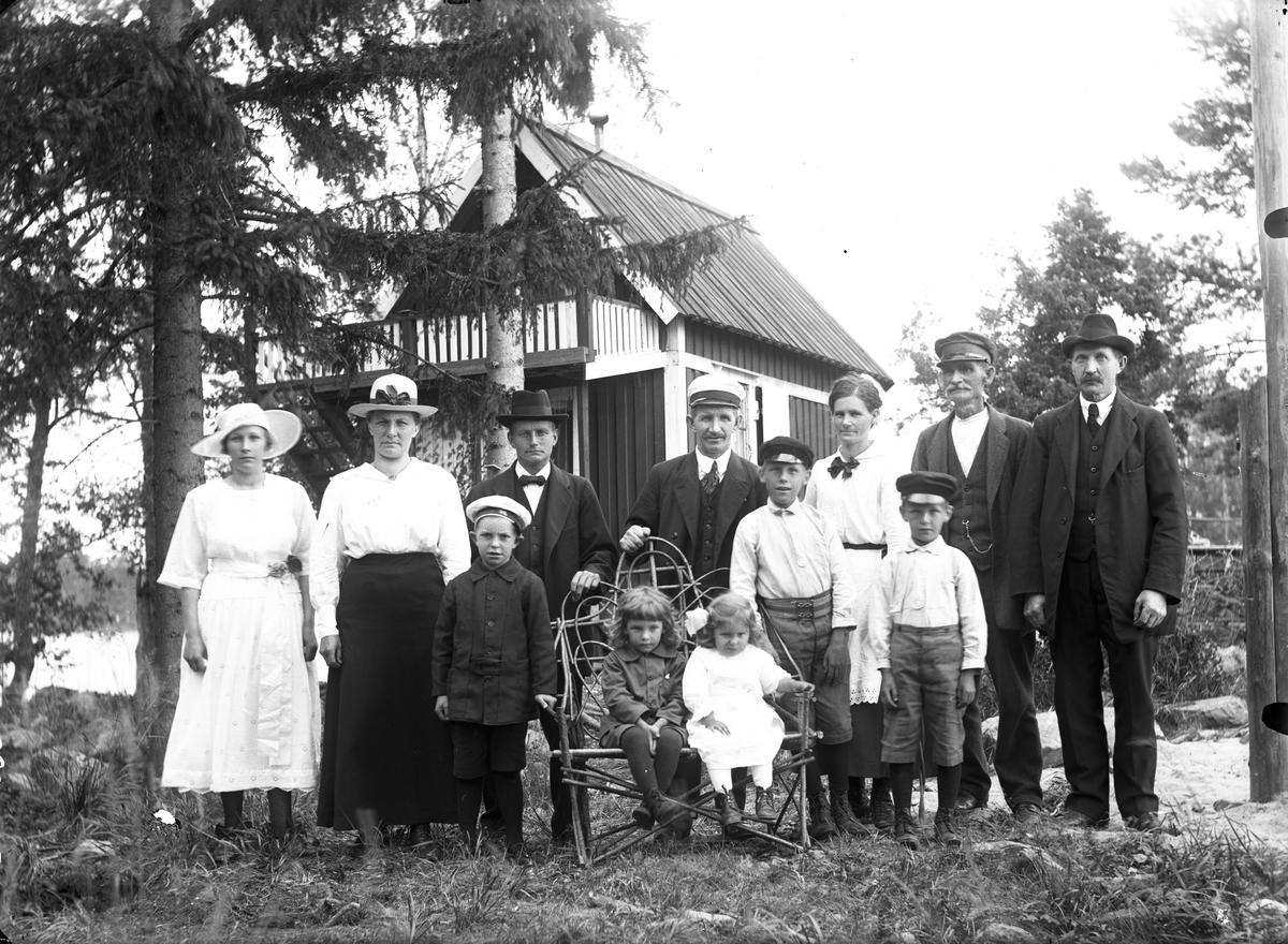 En grupp vuxna och barn framför ett bostadshus, lägg märke till stolen.
