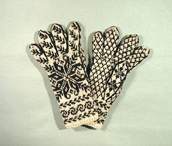 Ett par helmönstrade fingervantar med stjärnmotiv. Stickade i svart och vitt handspunnet ullgarn. Tummen och fingrarna både på utsidan som insidan är mönstrade ända ut i fingertoppen. Bladbård vid handleden.Typiskt för gotländska vantar är den helmönstrade stickningen.  Sökord: Ull.