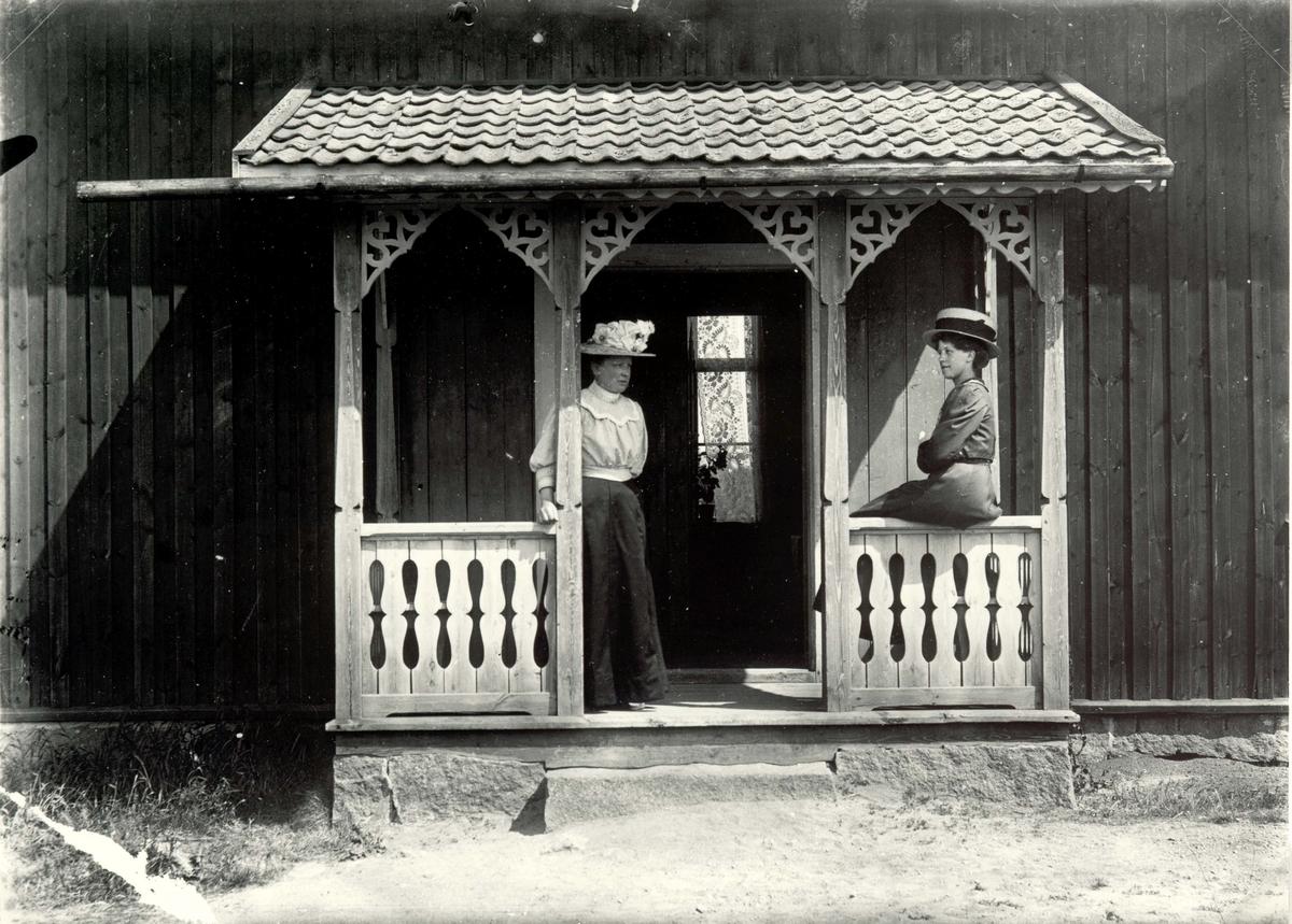 Två kvinnor i för tiden typiska kläder på verandan.