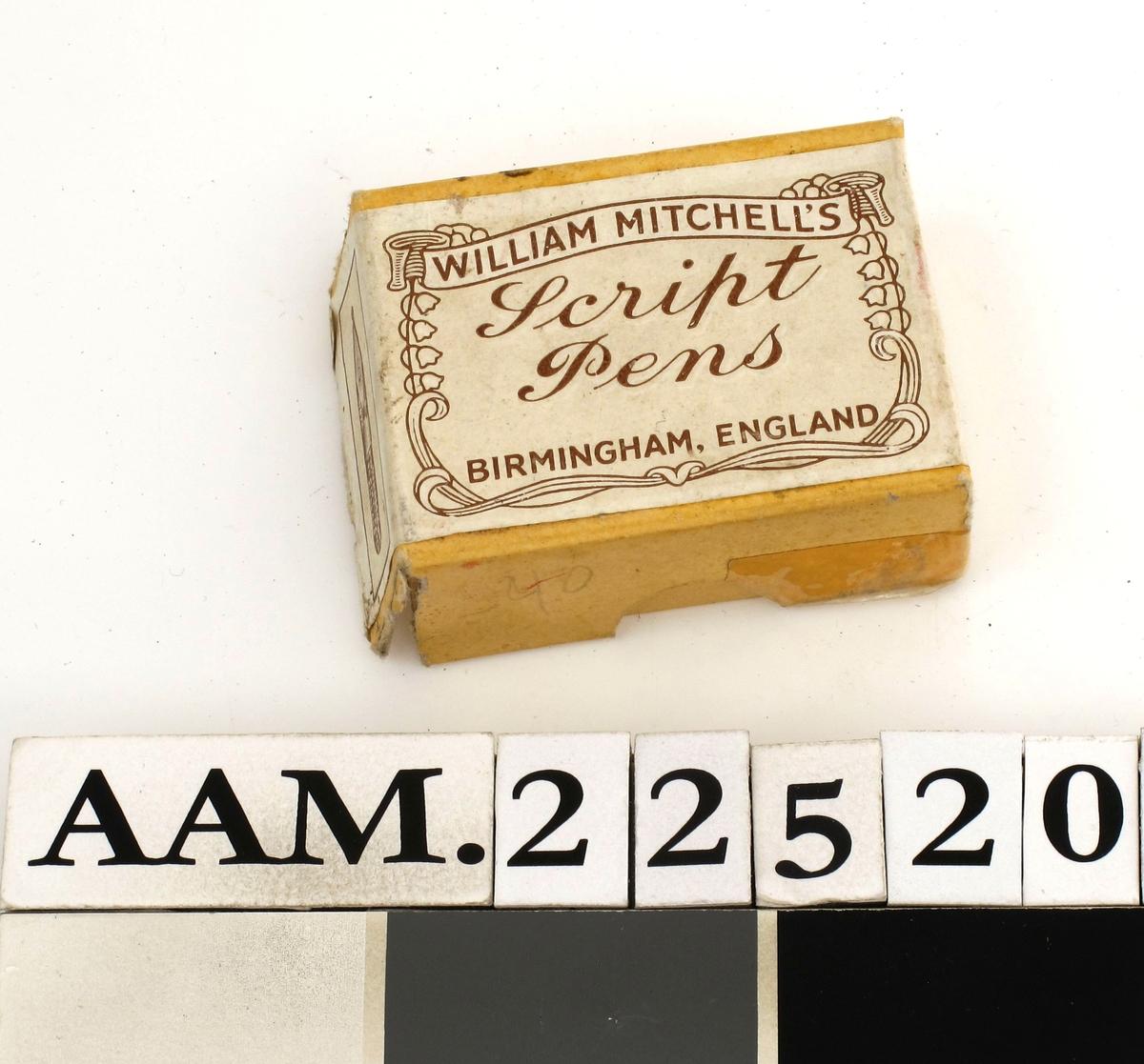 Pennesplitter i en eske. Papiretikett med design i jugend.  Eske fyllt av penner, de fleste  stål, noen messing. På lokket av den gule eske er en hvit etikett med brun tekst.  Etikett også på undersiden.