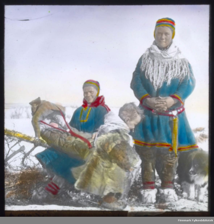 """""""N.549A9. Fjellsamer i Kautokeino"""" står det på glassnegativet. To samiske kvinner med sine barn er fotografert. Den ene sitter på en slede med et spebarn i komse. Barnet sover. Et litt større barn i pesk (reinsdyrpels) står foran i bildet. En samisk kvinne står oppreist. Begge er kledd i samisk kofte med sjal og lue. Kvinnen som står har en stor samekniv (storkniv) i beltet."""