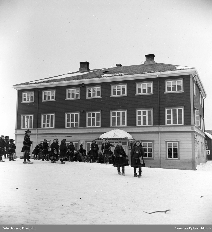 Skolebarn og muligens en lærer fotografert utenfor Kautokeino skoleinternat. Internatet var bygd i 1906, påbygd i 1932 og brant ned i 1944.