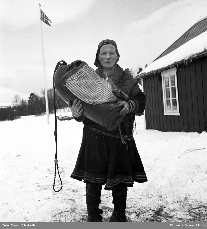 Susanne Aslaksdatter Siri med barnet i komse, utenfor en av Statens Fjellstuer. Muligens er dette Gargia Fjellstue. I bakgrunnen et norsk splittflagg på flaggstangen. Til høyre i bildet sees en bygning.