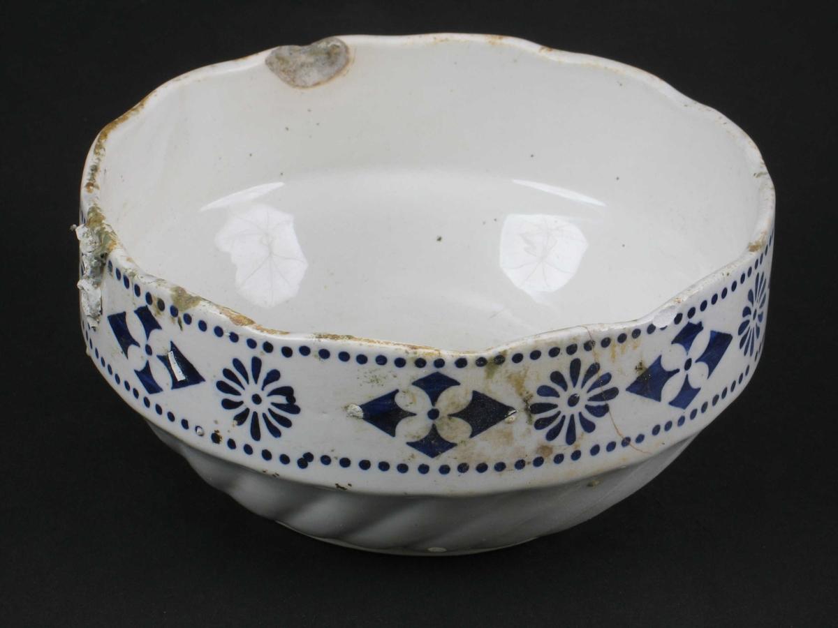 Bolle. Stentøy, hvit med blå bord. Bolle med svungne riller i nedre del, rettsidet  øvre del med ruter og blomster avgrenset av en  prikkbord på hver side.