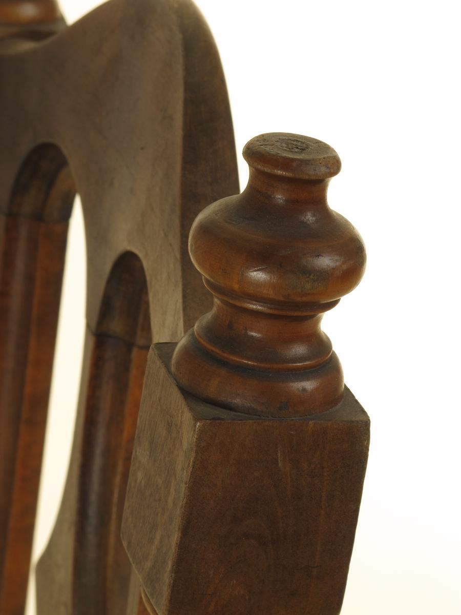 Bakstavene dreiet i ryggen, med spiler mellom, åpen og buet toppstykke. Setet treplate med små hull plassert i stjernemønster. Forbenene dreiet. Sargen buet ut i fronten.