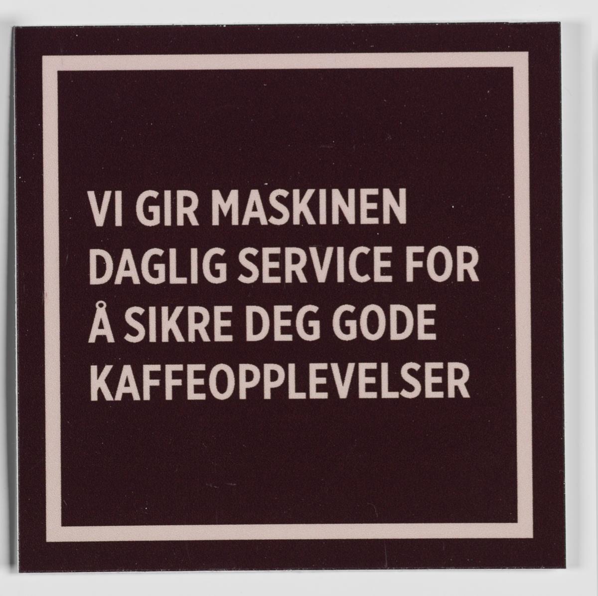 Et kvadratisk klistremerke med stilisert ramme med brun bunnfarge og beige tekst. Kan klistres på en flate i nærheten av kaffeautomaten i butikken.