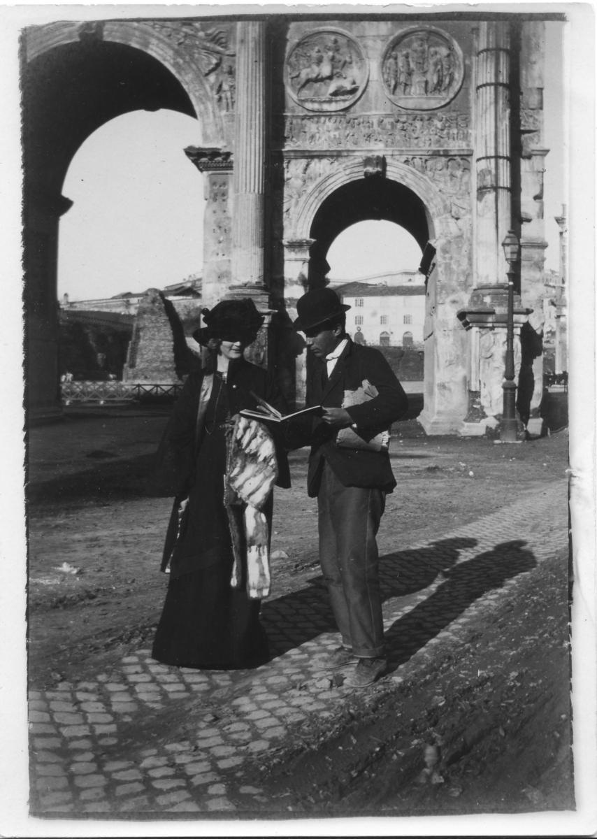 Ester Bauer tillsammans med en vykortsförsäljare framför Konstatini triumfbåge i Rom, Italien.