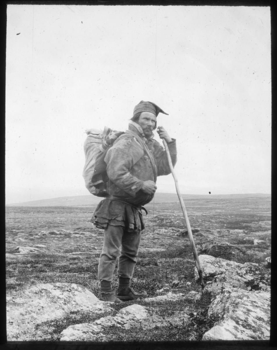 """""""N.355.) En fjellets sønn."""" står det på glassplaten. Portrett av samisk mann på vidda. Han bærer en bylt eller sekk på ryggen som er festet skrått over brystet. Han er kledd i samisk drakt og lue, med skaller sydd i skinn p beina, og skallebånd rundt anklene. I hånden holder han en vandrestav eller stokk. Vidda ligger bak han så langt øyet rekker og det er sommertid."""