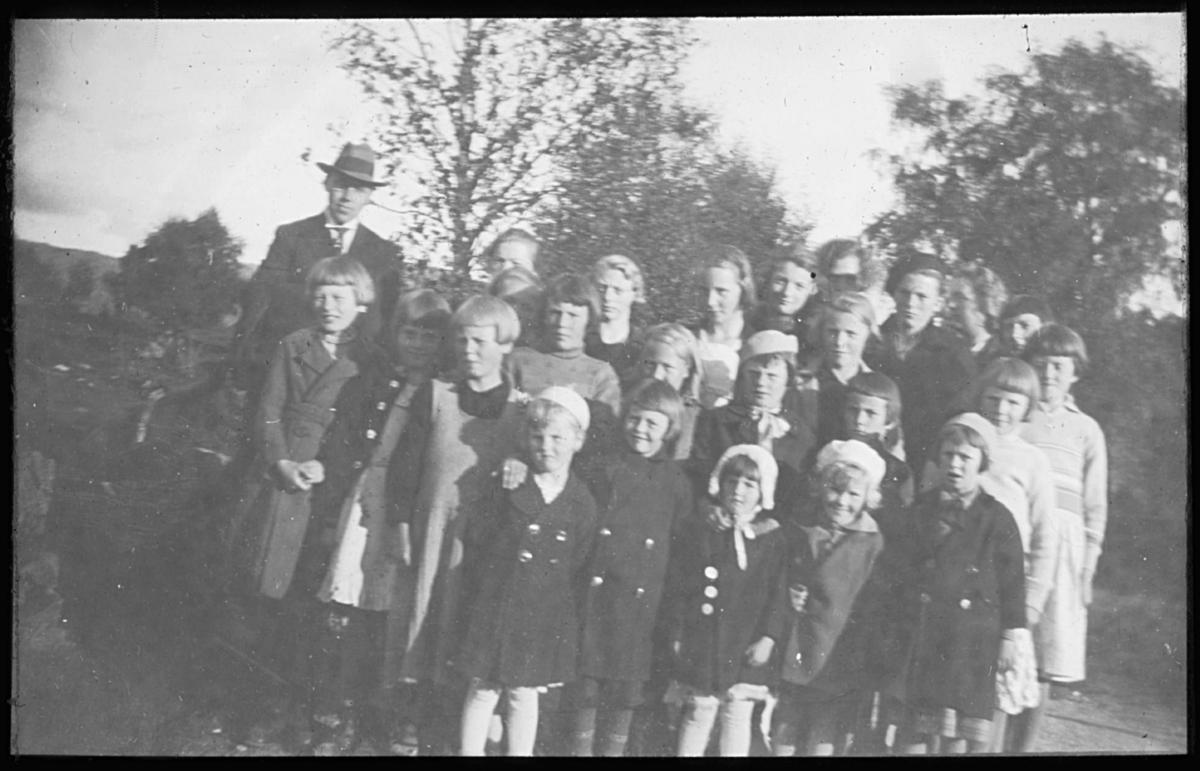 Gruppeportrett av små jenter i kåper og hatter. En mann med hatt står bakerst til venstre.  Noen av ungene har dobbeltspente kåper og hatter/kyser. Muligens et barnehjem? Alf Schrøder har dokumentert flere barnehjem i Finnmark, ref. Norsk Finnemisjons (senere Samemisjonens) barnehjem.
