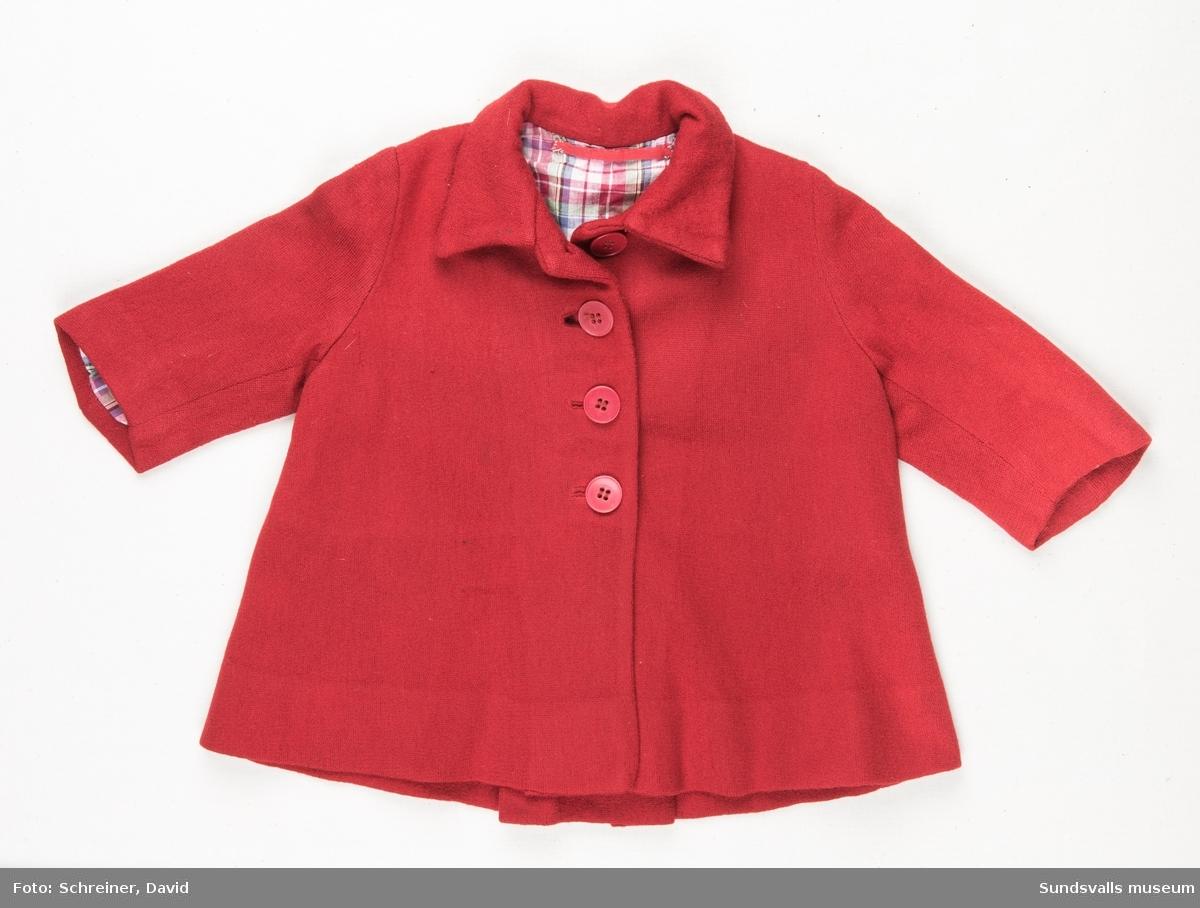 En röd A- formad kappa till flicka i 3-års åldern. Kappan har en rundad krage, dekorsöm och bälgveck baktill. Den övre halvan knäpps med fyra röda plast knappar. Kappan har ett smårutigt tunt bomullsfoder.