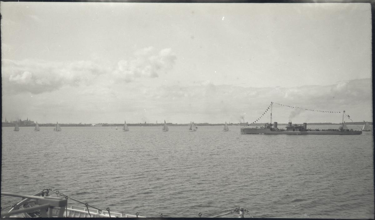 Vy av Tallinn från vattnet med mindre segelbåtar samt en jagare med stor flaggning. Jagaren är av Izjaslav-klass och bör därför vara LENNUK, ex AVTROIL, som tillföll Estland efter första världskriget. Bilden är tagen i samband med Gustaf V:s statsbesök i Tallinn i juni 1929.