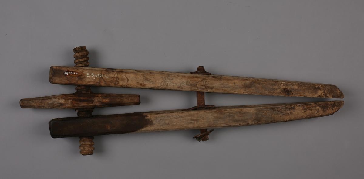 Båttvinge i v-form hvor skrue i ene ende er laget av tre. Jernbolt på midten.