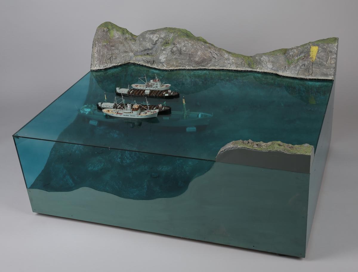 Bjergningsmodell i tre deler av et sunkent 7 000 tonns lasteskip.  Viser hvordan bjergningen blir gjennomført med hjelp av bjergningsbåter og løftelektere.