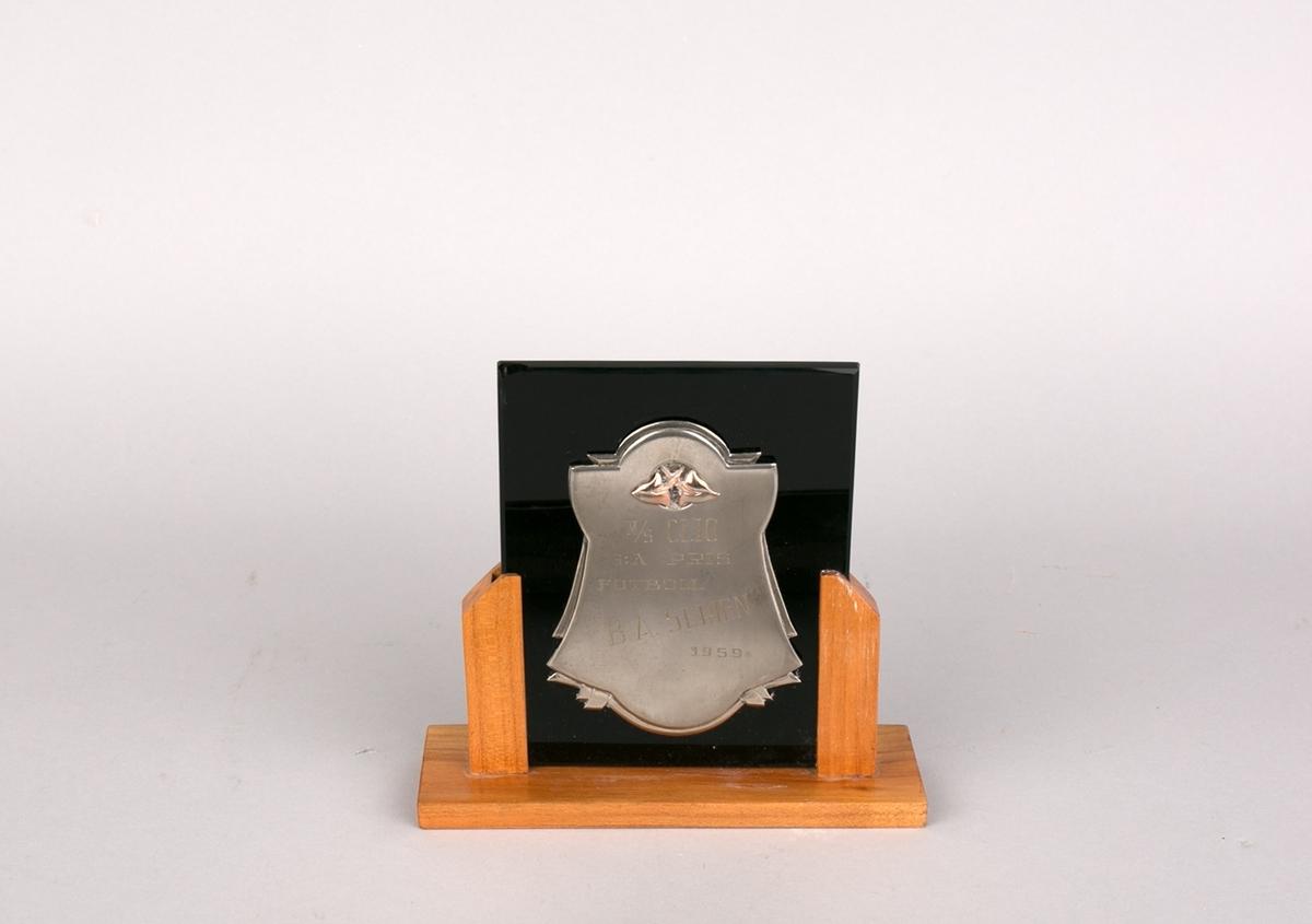 Plaket gitt MS CLIO i 1959. Tekst inngravert montert på glassbakgrunn i trestativ/sokkel.