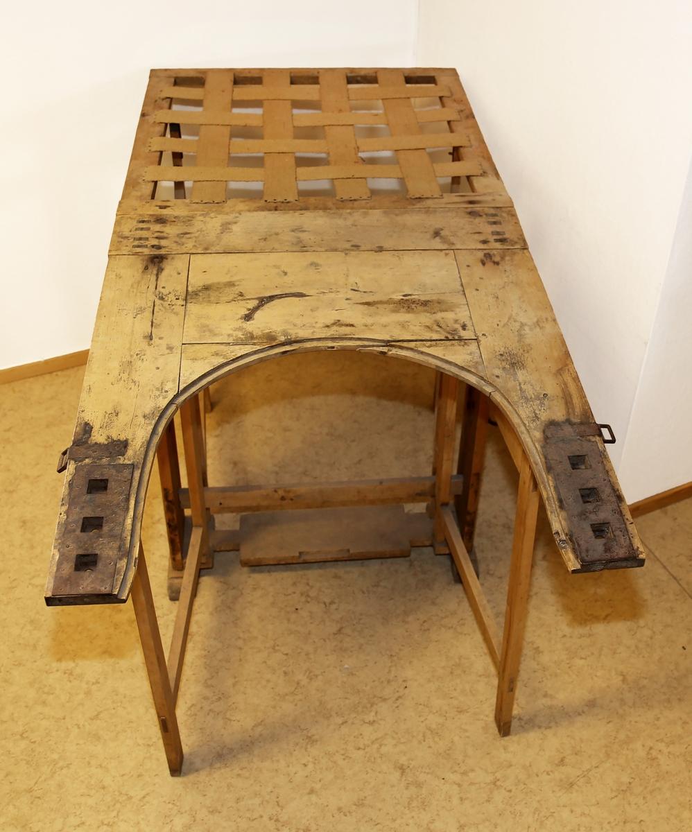 Stol av tre der ryggen både kan heises opp og legges flat og der sitteflaten er uthulet slik at bena kan hvile på sidestykkene og barnet kan tas imot i åpningen mellom.