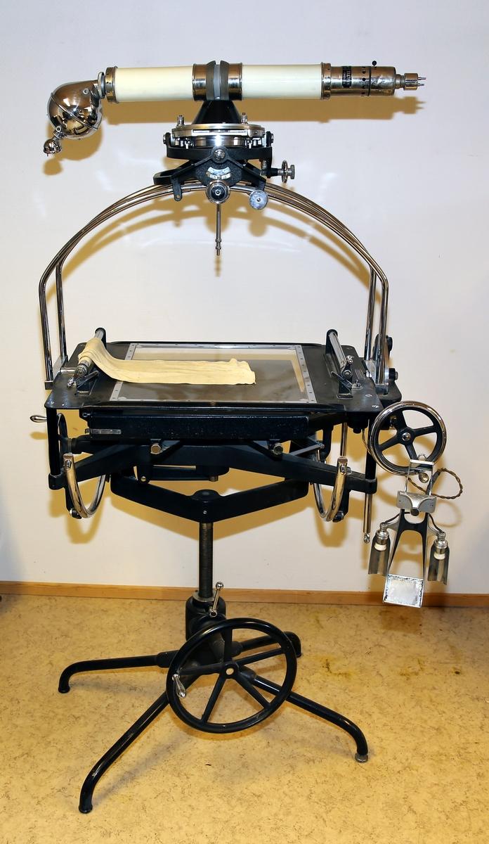 Glassbord på metallstativ med røntgenapparat over som kan rotere