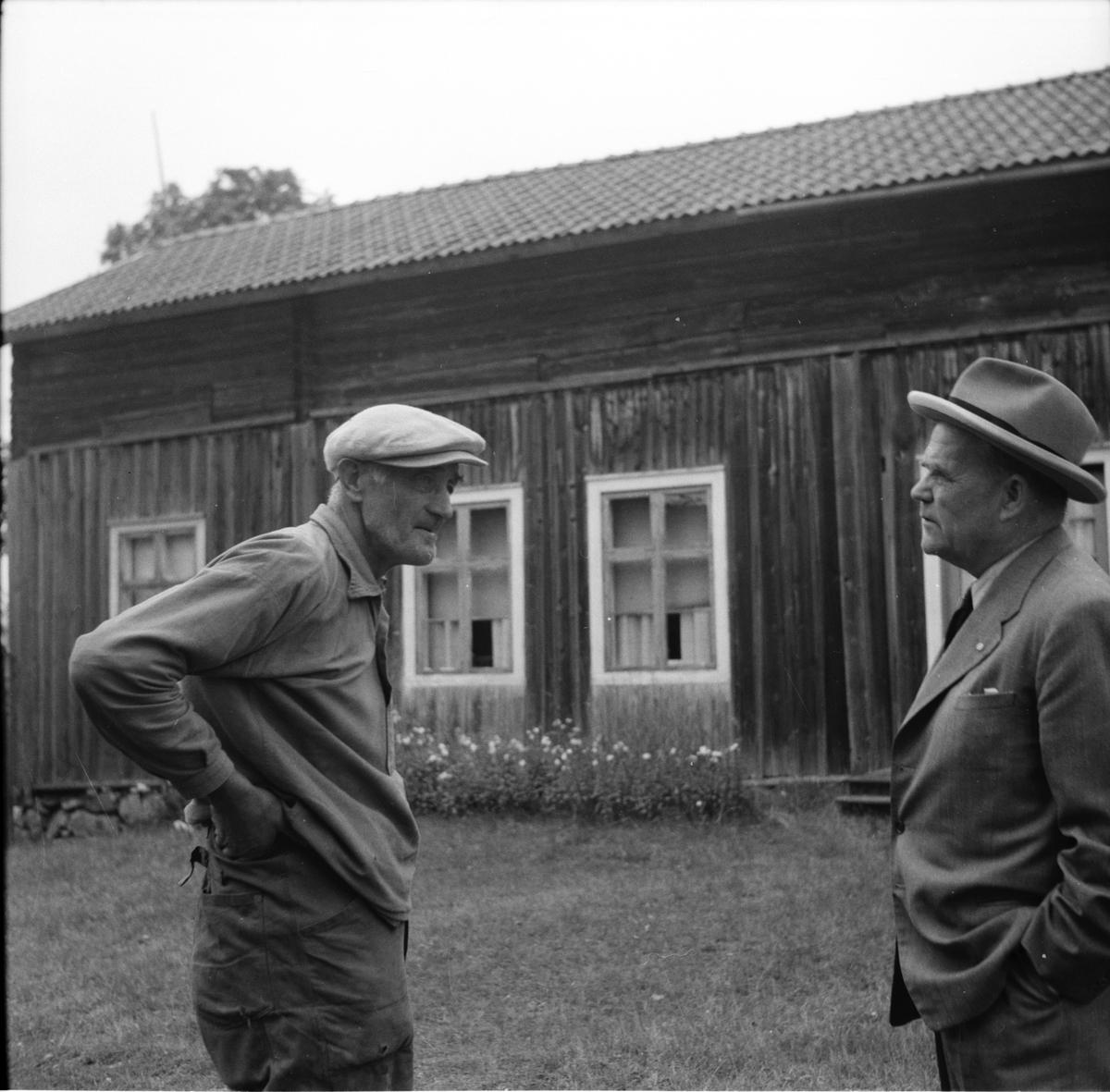 Två herrar samtalar. Hans Mickelsson till vänster.