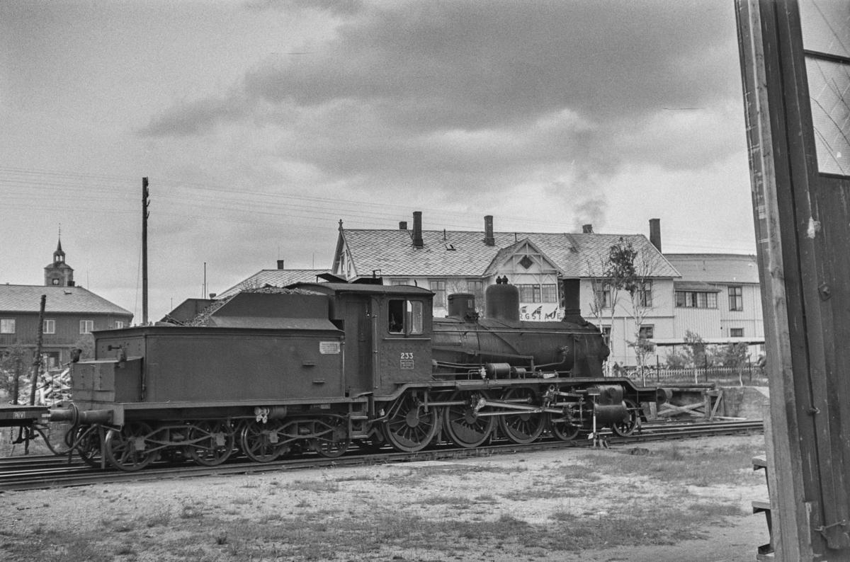 Damplokomotiv type 18c nr. 233 i sydgående godstog på Røros stasjon. I bakgrunnen gamle Bergstadens hotell.