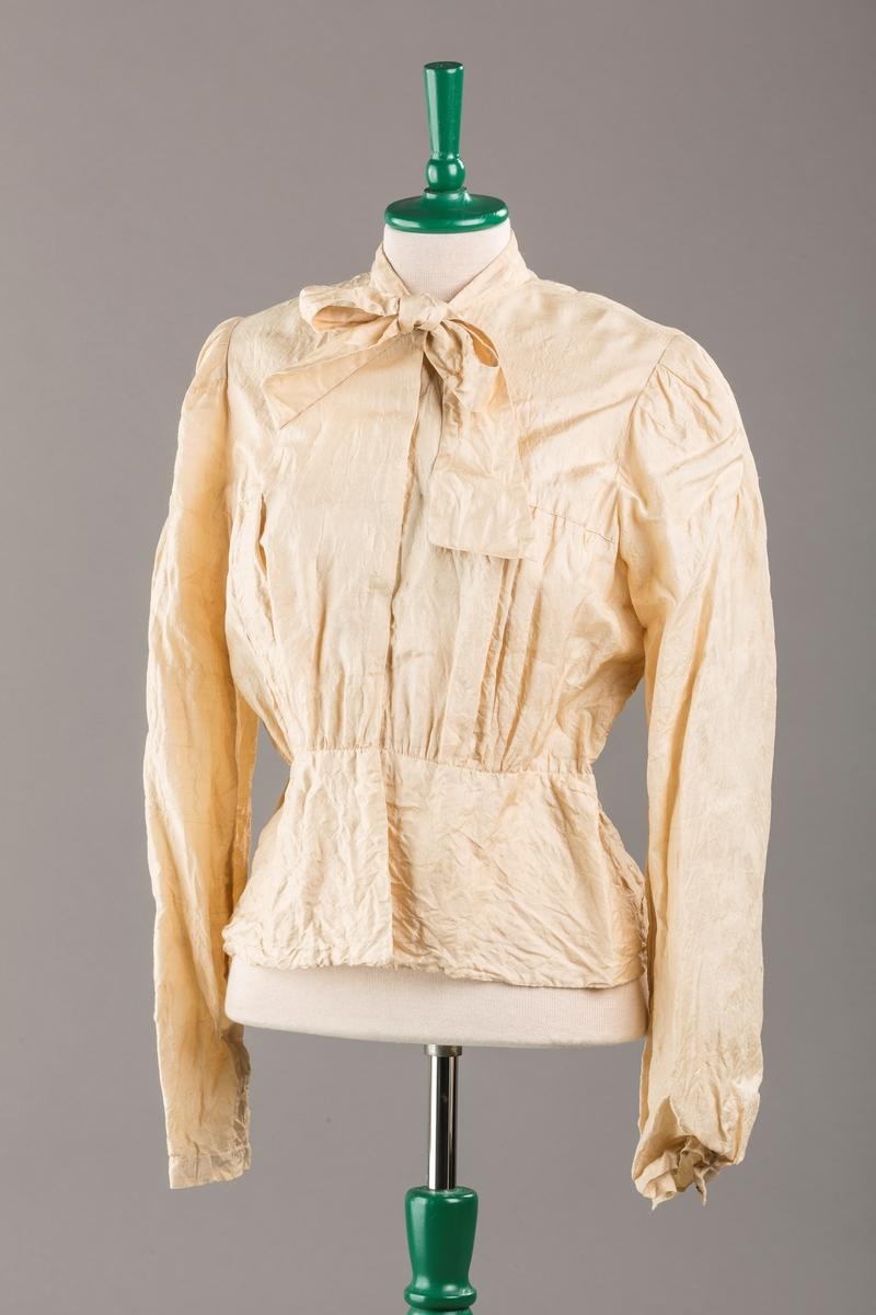 Bluse med sløyfe i halsen og kappe nederst, 9 trykknapper, leggsying på ryggen.