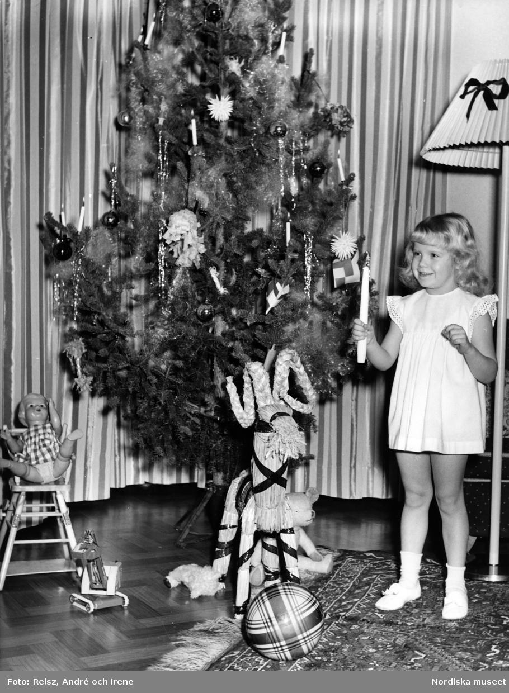 Flicka i ljus klänning håller i ett ljus bredvid en julgran