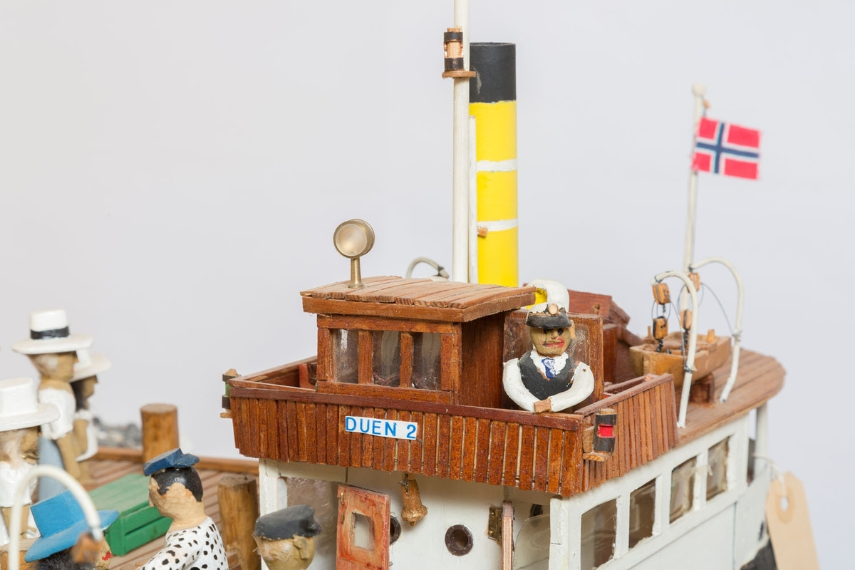 """Modellen av """"Duen 2"""" ble bygget 1993, og er Bækvolds byggenummer 36.  """"Duen"""" gikk som """"Pappabåt"""" fra Festningskaia til Vollen og Sætre, modellen viser den ved ventebua på Vollen brygge. Laster grønne kasser med bringebær.  Dampbåt kjøpt i Tyskland 1920. Laste- og passasjerbåt. Isbryter med skrog av klinkete jernplater."""