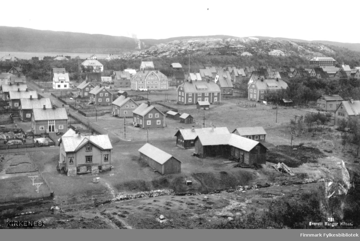 Bildet viser et parti fra Kirkenes etter postkort av Magnor Nilsen fra ca. 1930. Gaten til venstre er Karl Lunds gate.
