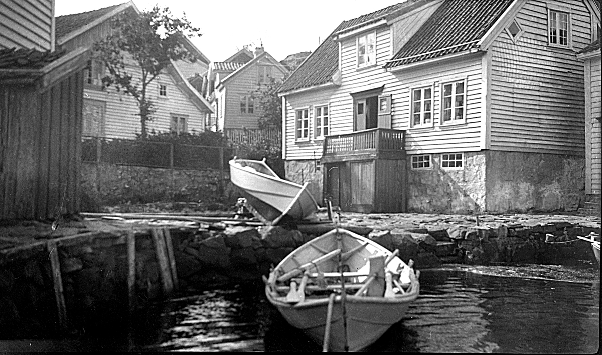 Nedenfor Rennesåga i Loshavn ligger en båt fortøyd. En annen båt er dratt på land foran et hus.