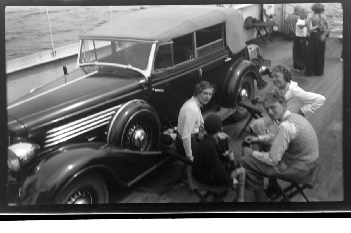 Hilda Sundt, Lars Peter Sundt, Julius Sundt og en ukjent person sitter ved siden av Rolf Sundt sr.'s nye Buick ombord på fergen mellom Langesund og Helgeroa. Fotografert 17. juli 1938. Buick årsmodell 1934-35, convertible sedan karossseri.