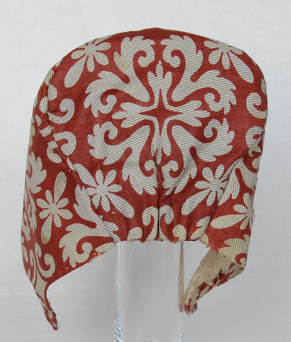 """""""Flatmössa"""" med linnefoder i tuskaftsbindning och mönstrat bomullstyg i rödbrunt, vitt och blått utanpå. Mössan är sydd med nackstycke."""