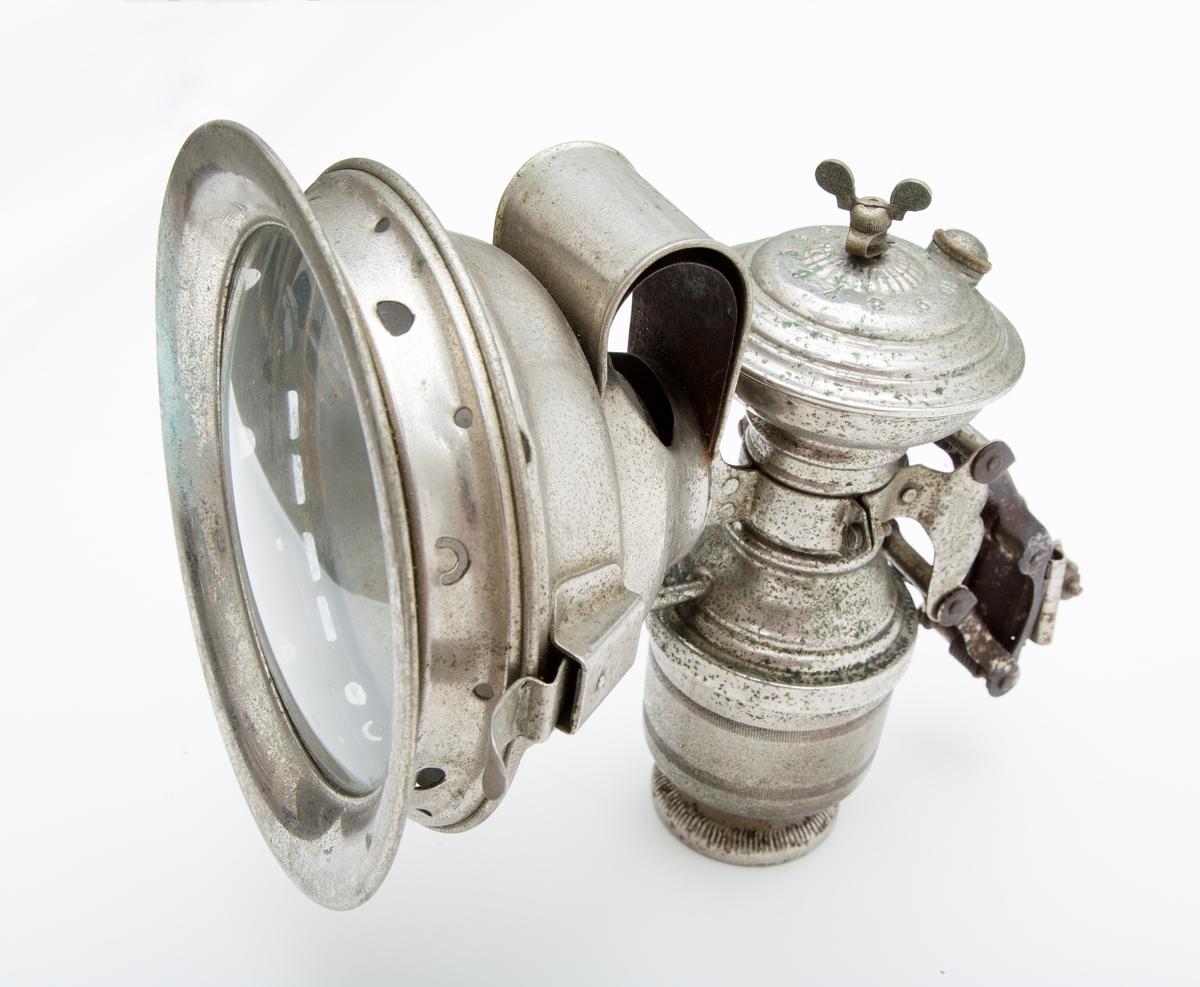 Transportabel lykt med reflektor og vannbeholder. Har klemmefeste, antakelig for sykkel eller motorsykkel (?), drivstoff kalsiumkarbid.