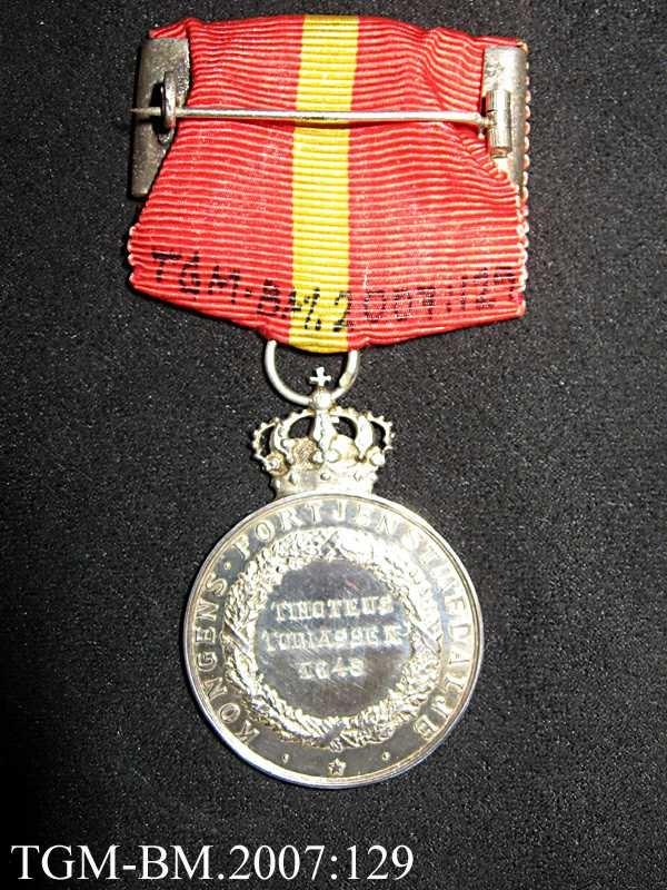 Medaljen ligger i en liten, flat, burgunderrød eske (original-etui) - preget med en forgylt krone på lokket. Silke og fløyel innvendig.