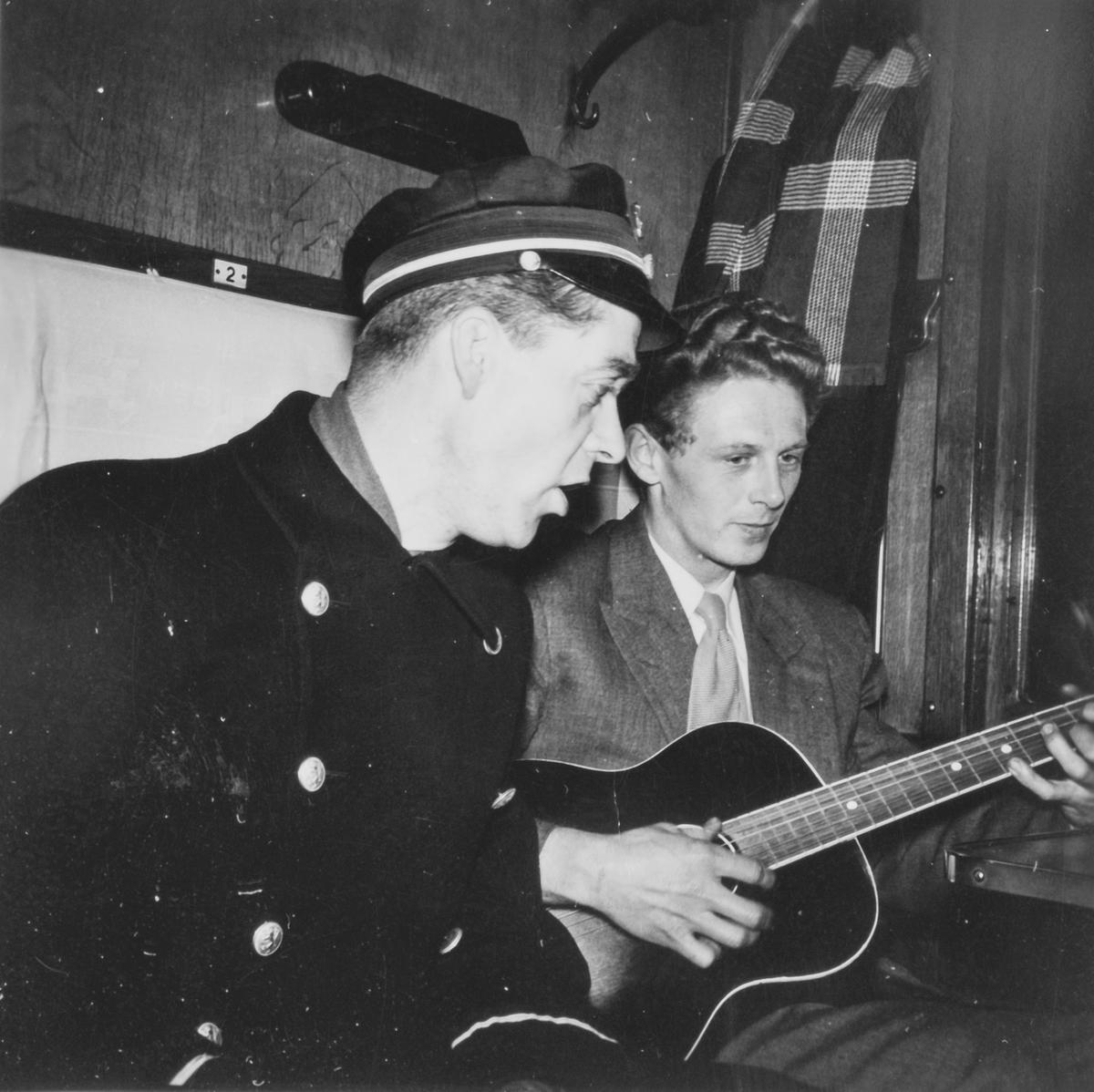 En jernbanemann og en reisende i en 2. klassekupe på Nordlandsbanen.