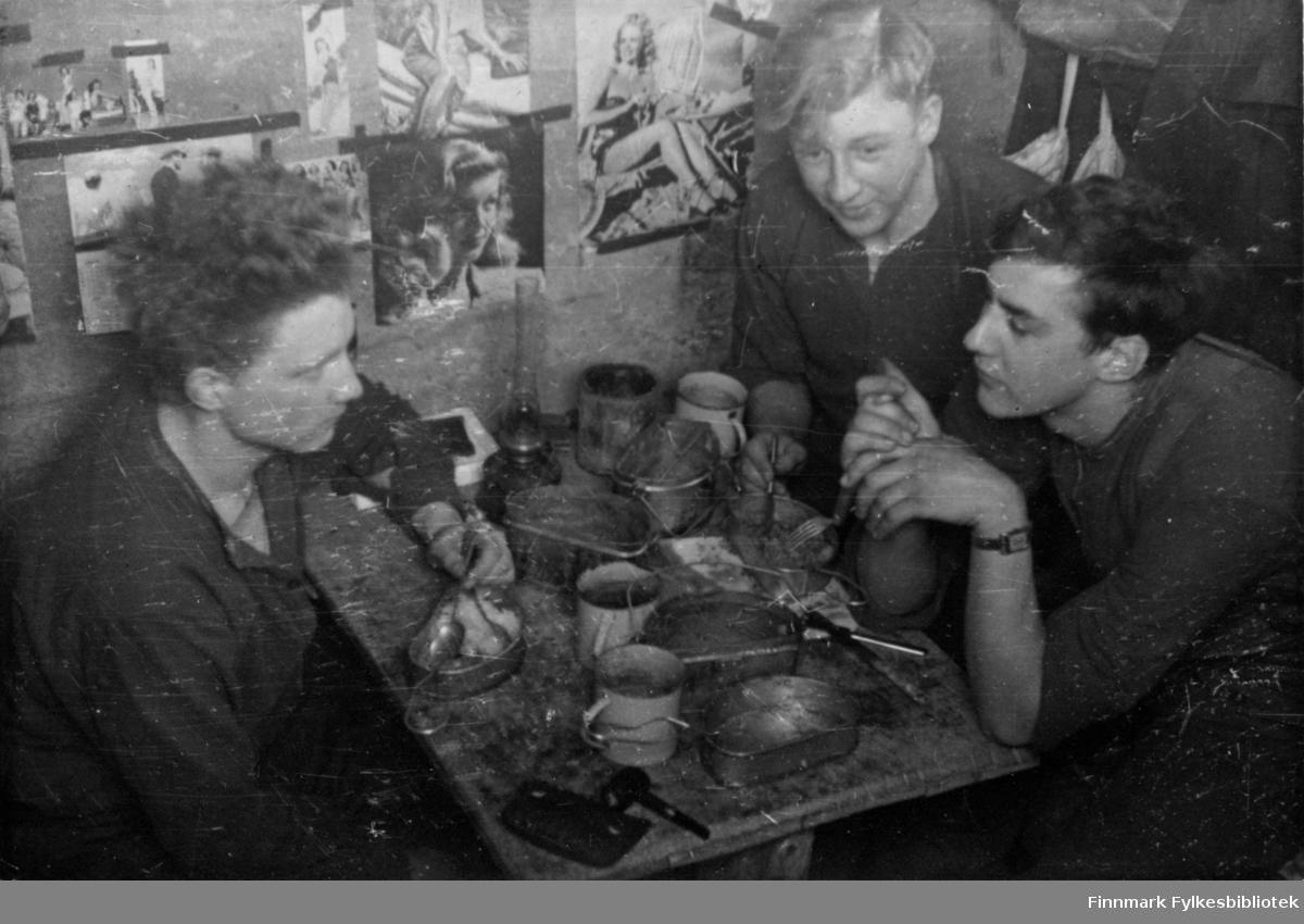 """Frokost. Tre soldater fra Sambandstroppen. På veggen er det hengt opp datidens filmstjerner. Bildet kan være tatt i Skottland før avreise eller på slutten av krigen. Soldatene har emaljekopper og blikk matdåser,  Bildeserien """"Frigjøringen av Finnmark 1944-45"""" viser et unikt materiale fotografert av soldater i Den Norske Brigade, 2. Bergkompani under deres oppdrag """"Frigjøringen av Finnmark"""" som kom i stand under dekknavn """"Øvelse Crofter"""". Fakta rundt dette bildematerialet illustrerer iflg. vår informant, George Bratli: """"2.Bergkompani, tilhørende Den Norske Brigade i Skottland,  reiste fra Skottland 30. oktober 1944 med krysseren «Berwick» til Scapa Flow på Orkenøyene for å slutte seg til en større konvoi som skulle være med til Norge. Om bord på andre skip var det mange russiske krigsfanger som hadde vært på tysk side og som nå ble sendt hjem.  2.Bergkompani forlot havn 1.november 1944 og kom til Murmansk, Sovjetunionen, 6. november 1944.  De ble her lastet om og fraktet til Petsamo, Sovjetunionen, hvor de ankommer 11.november 1944.  Kompaniet reiser så til Sandnes utenfor Kirkenes og blir forlagt der frem til 26.november 1944. De flytter så videre til Skipparggura.  Den 29.november reiser deler an kompaniet til Rustefielbma og Smalfjord og noen drar opp på Ifjordfjellet.   17. desember ankommer resten av kompaniet til Smalfjord. 30.desember blir en avdeling sendt til Hopseide og 8. januar 1945 blir noen sendt til Kunes. Den 14. januar er kompaniet delt og ligger i Kunes, Kjæs, Børselv, Hopseide og Smalfjord. 5. februar 1945 blir 3.tropp sendt over Porsangerfjorden for å operere i Olderfjorden. Her var de i kamp og hadde tap i  Billefjord og Sortvik. 8.mars 1945 kom noen til Renøy og 12. mars kom første del av kompaniet til Brennelv. 7.mai begynte kompaniet å bygge ny kai i Hambukt. 19. mai ble de som hadde falt begravd i Lakselv. 8. juni ble kompaniet flyttet fra Brennelv til Tromsø for så å bli sendt videre til Mo I Rana 16.juni."""""""