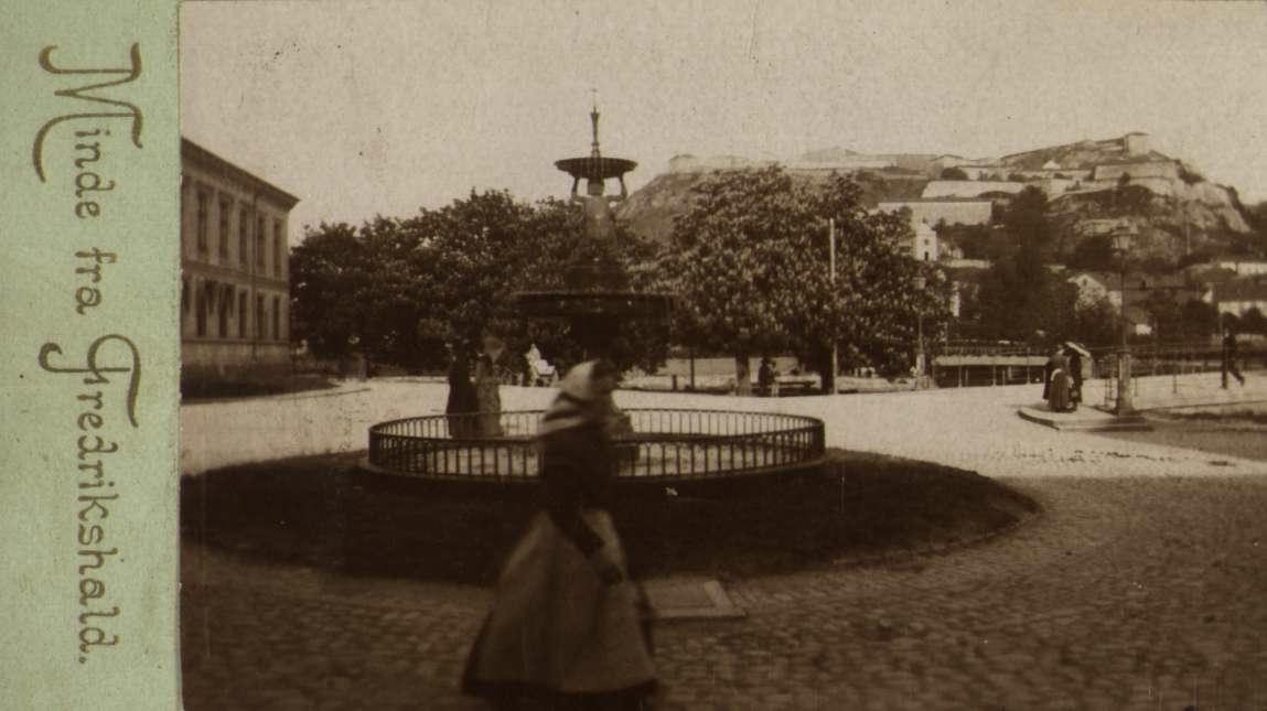 """Nyttårskort. Fotografisk motiv. Kvinne foran fontene på et torg. Fredrikshald festning i bakgrunnen. Påtrykt tekst: """"Minde fra Fredrikshald"""". """"Olaf S. Madsen""""."""